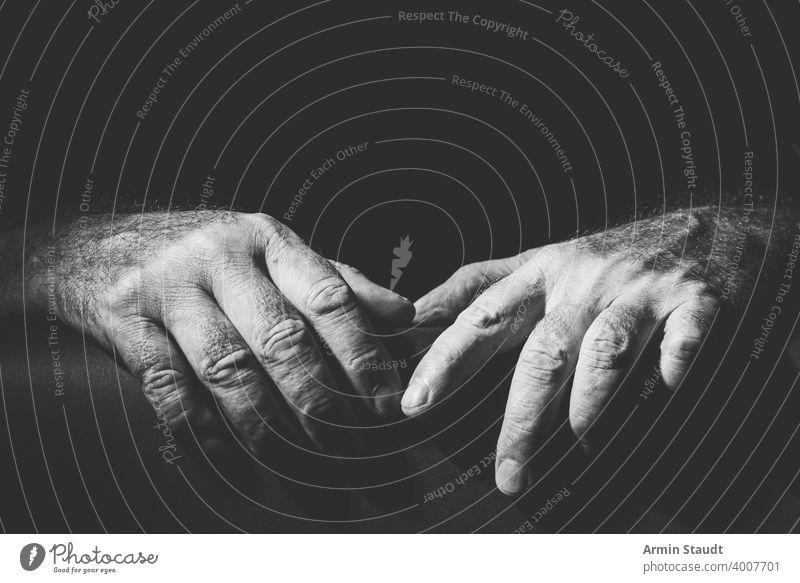 zwei entspannt nebeneinander liegende Hände Erwachsener schwarz schwarz auf weiß hell bw Nahaufnahme enthalten Kontrast dunkel Umarmen Ausdruck Finger