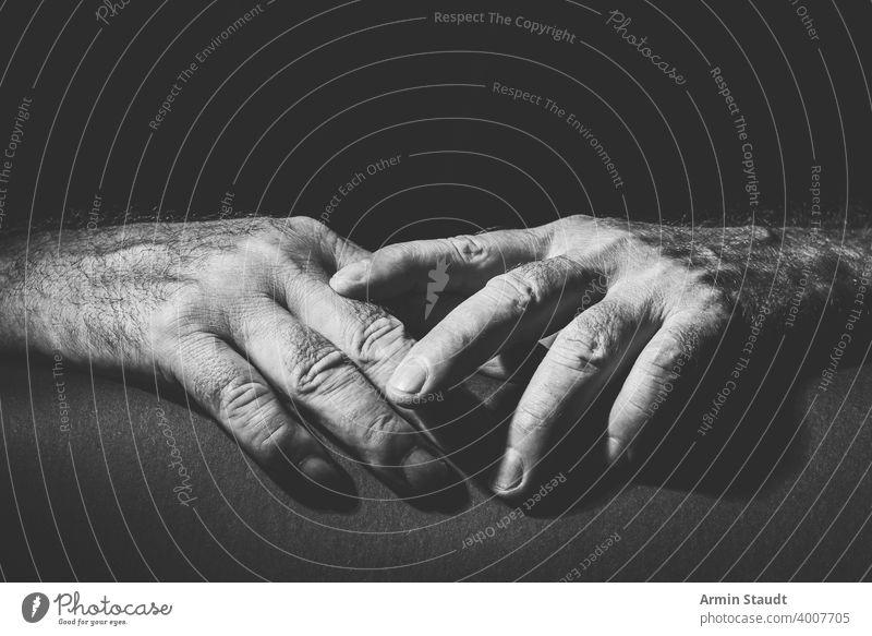 zwei entspannt übereinander liegende Hände Erwachsener schwarz schwarz auf weiß hell bw Nahaufnahme enthalten Kontrast dunkel Umarmen Ausdruck Finger