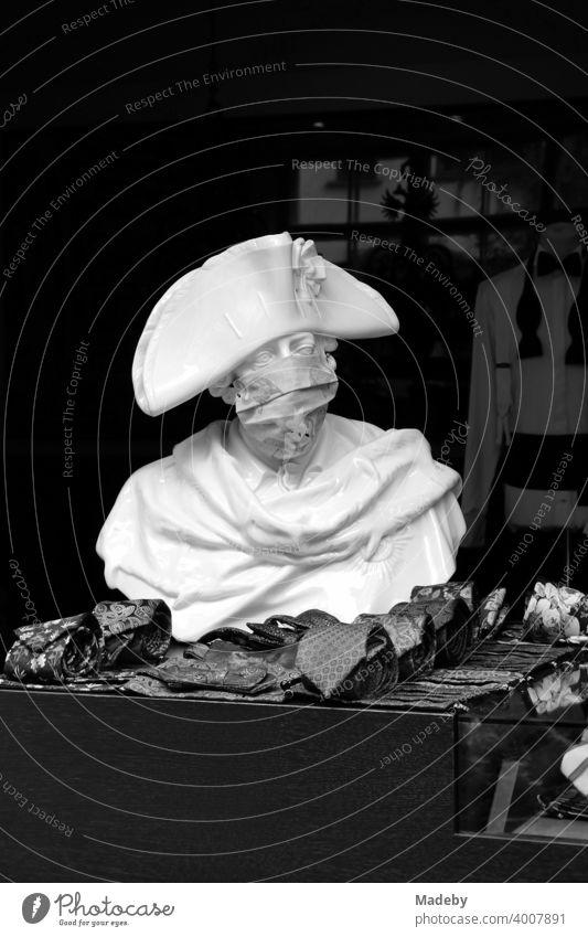 Büste Friedrich des Großen mit Mundschutz vor dem Geschäft eines Herrenausstatter in den Hackeschen Höfen am Hackeschen Markt in der Hauptstadt Berlin, fotografiert in neorealistischem Schwarzweiß