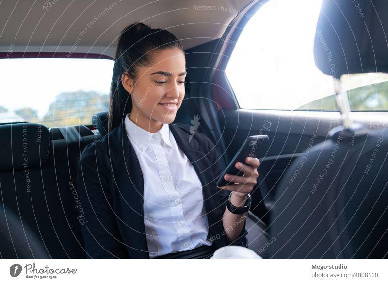 Geschäftsfrau benutzt Mobiltelefon im Auto. Frau PKW Mobile Telefon Taxi Transport Kabine männlich eine Porträt Erwachsener professionell zur Arbeit gehen