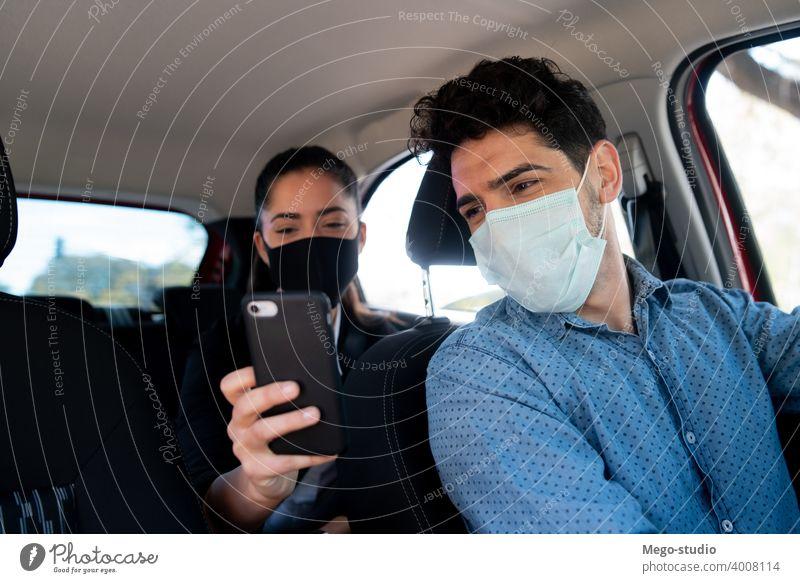 Frau zeigt dem Taxifahrer etwas auf dem Telefon. Mann Geschäftsmann Mobile PKW Gesicht Mundschutz Transport Kabine männlich eine Porträt Erwachsener