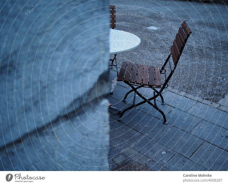 Blick um die Ecke auf Bistrostühle und Tisch-ein geschlossenes Straßencafe Stuhl Stühle tisch Sperrung Coronavirus Korona Restaurant COVID Virus Vorsorge