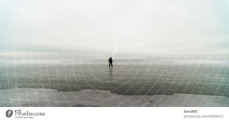 Silhouette eines einsamen Mannes auf Eis im gefrorenen Meer Hintergrund Strand Klima Wolken wolkig Küste Küstenlinie kalt Tag dreckig Frost gefrorenes Meer