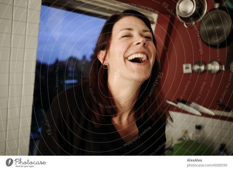 junge Frau steht in ihrer Küche und lacht herzlich lachen glücklich küche schoen groß verrotten Töpfe schlank emotional Gesicht Erwachsene Identität sportlich