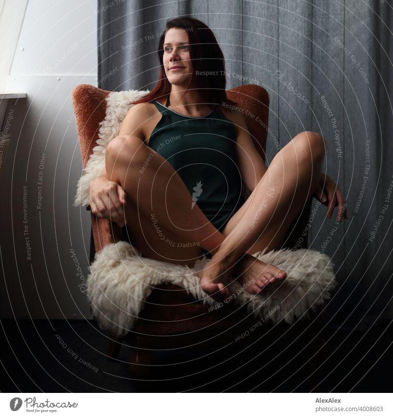 junge Frau sitzt im Schneidersitz auf einem Sessel mit Schaffell und schaut auf dem Fenster Beine barfuß langbeinig lachen petrol Kleid Vorhang Haut Farbfoto