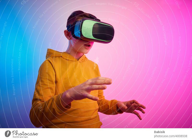 Junge mit Virtual-Reality-Brille auf buntem Hintergrund. Zukunftstechnologie, VR-Konzept Headset virtuell Realität Schutzhelm Technik & Technologie Gerät Spiel