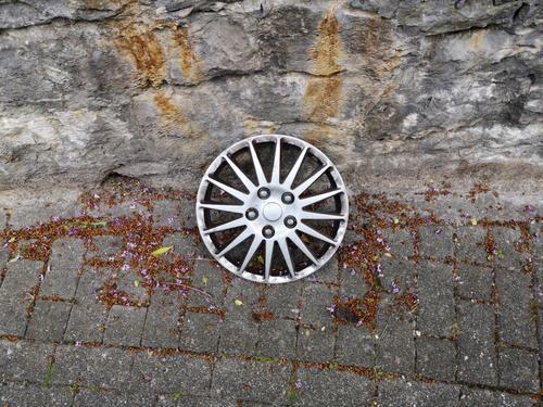 Verlorengegangene silberne Radkappe im Stil einer Leichtmetallfelge auf altem grauen Straßenpflaster vor Mauerwerk aus Naturstein in Oerlinghausen bei Bielefeld im Teutoburger Wald in Ostwestfalen-Lippe