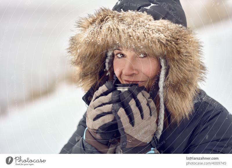 Glücklich lächelnde Frau trägt einen Pelz getrimmt Kapuzenjacke genießen einen Becher Kaffee in ihren behandschuhten Händen im Freien im Winter Schnee in einem Konzept der Jahreszeiten in einer Nahaufnahme Porträt Wiegen