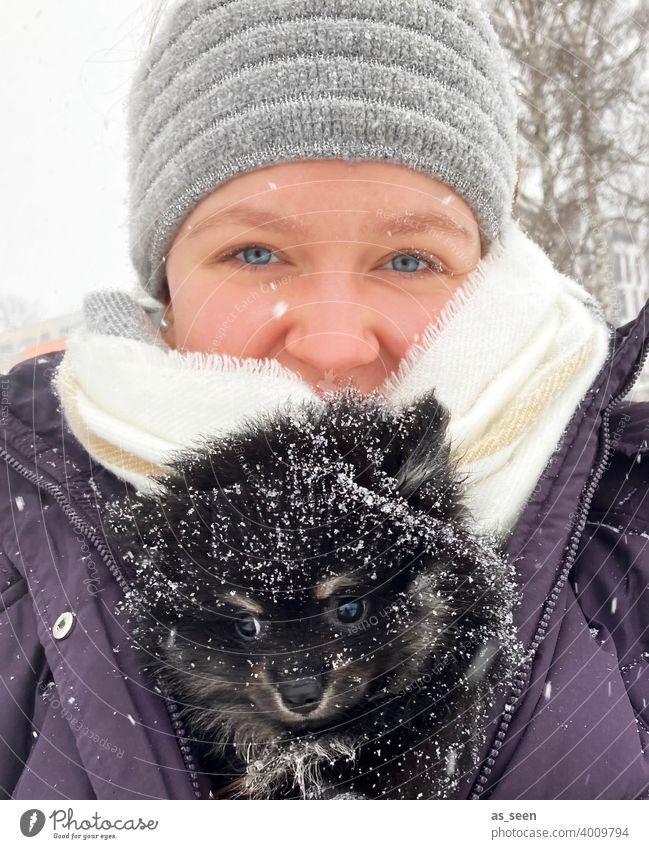 Junge Frau trägt Black Pomeranian Welpen durch den Schnee Zwergspitz Hunderasse blaue augen Blick in die Kamera Freude Tierliebe Schneeflocke Farbfoto