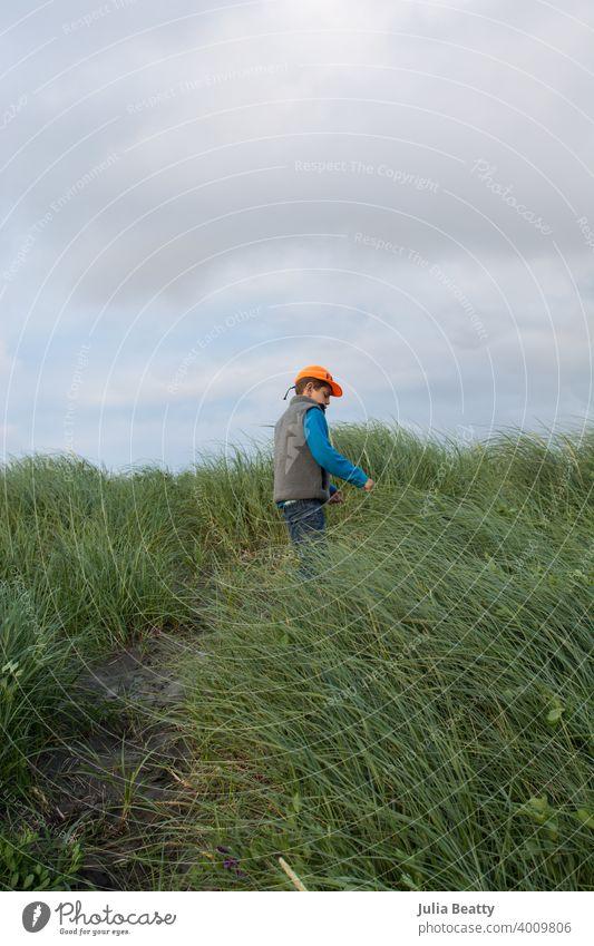 Junger Junge klettert eine Sanddüne mit Gräsern am Strand an einem kalten Tag Sandhügel Gras Strandhafer Aufstieg Abenteuer Kind wolkig Oregon Küste pazifik