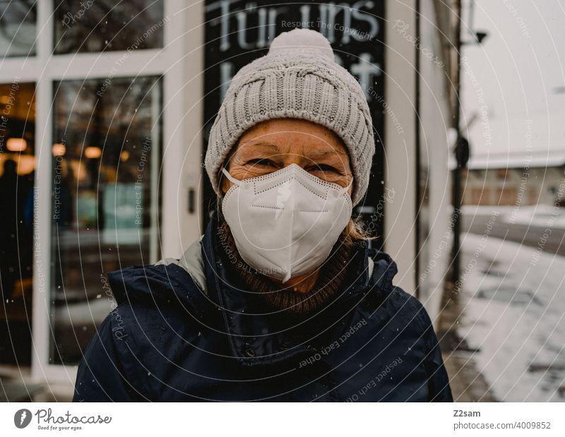 Frau mit Maske vor Geschäft corona pandemie maske COVID Infektionsgefahr Coronavirus covid-19 Schutz Mundschutz Prävention einzelhandel geschäft zusammenhalt