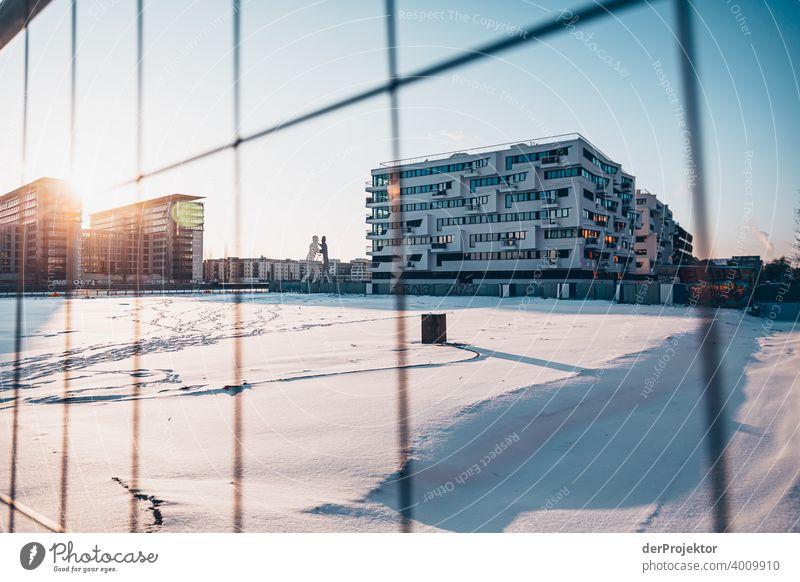 Molecule Man im Winter mit Neubau Mauer Wand trendy Licht Tag Textfreiraum Mitte Außenaufnahme Experiment Textfreiraum oben Berlin Farbfoto Himmel (Jenseits)