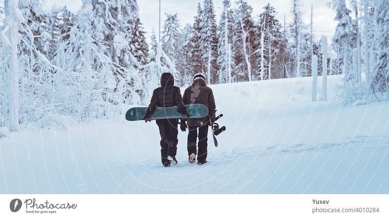 WEB-Banner-Format. Zwei Freunde Snowboarder sind zu Fuß durch den Winterwald. Snowboarden im Wald in den Bergen. Backcoutry oder Freeride-Stil. Lebensstil.