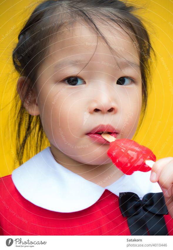 Kleine Mädchen in rot Student gekleidet Essen ein rotes Eis am Stiel Stieleis wenig niedlich süß essen jung Hintergrund Lebensmittel Glück Spaß Dessert Sahne