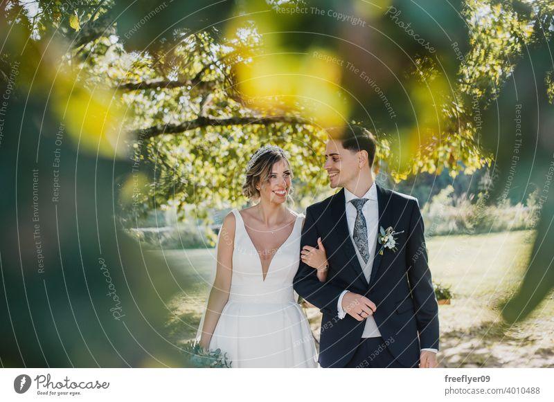 Junges Paar schaut sich an ihrem Hochzeitstag an Heirat Engagement Braut Menschen jung attraktiv Textfreiraum striegeln Baum Natur Außenseite Sonnenlicht Sommer