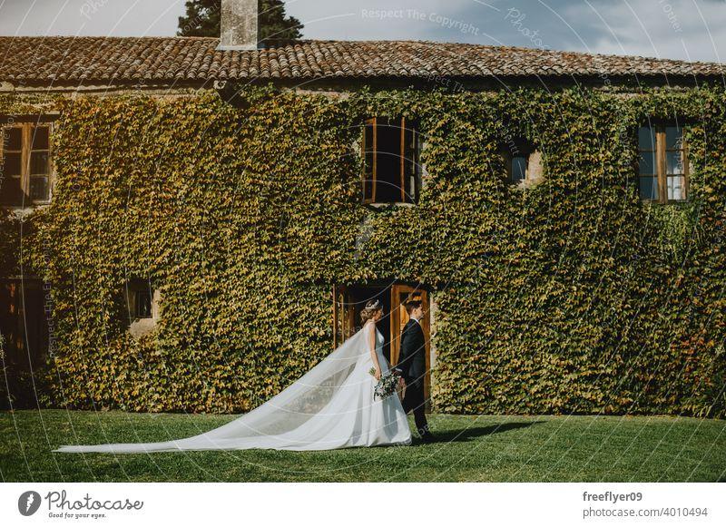 Ehepaar am Hochzeitstag vor einer Wand voller Kletterpflanzen Heirat Engagement Braut Menschen jung attraktiv Textfreiraum pazo Galicia antik Burg oder Schloss