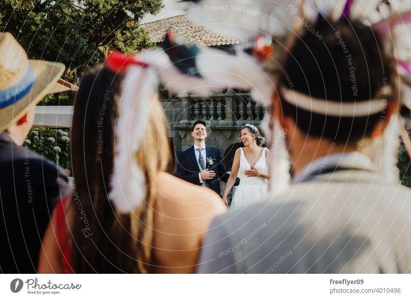 Paar lachend bei einer Hochzeit mit verkleideten Gästen Heirat Engagement Braut Menschen jung attraktiv Textfreiraum Party Spaß 20s genießend Grimasse