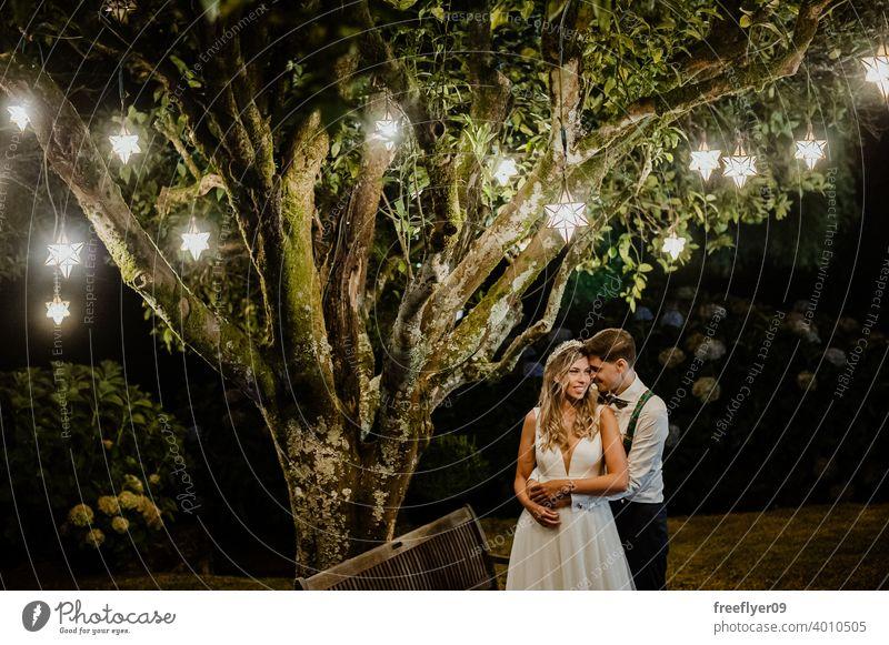 Ehepaar unter einem Baum an ihrem Hochzeitstag Heirat Engagement Braut Menschen jung attraktiv Textfreiraum Nacht Lichter Schmuckanhänger Natur außerhalb Liebe