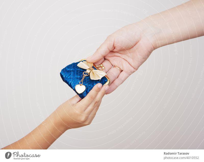 Hände der Mutter gibt die Geldbörse an ihre kleine Tochter Mädchen Hintergrund Frau schön Glück attraktiv Menschen Person weiß Schönheit Porträt Stil Lächeln
