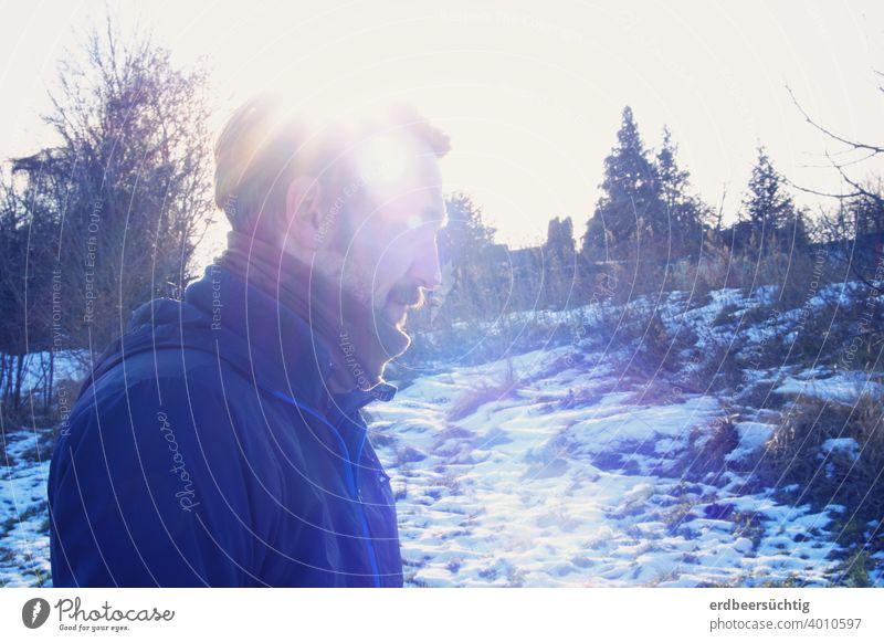 Mann in kalter Winterlandschaft mit Sonnenstrahlen-Mütze Landschaft profilbild blau weiß Frost Strahlen Schal Schnurrbart Licht Eis Kälte frieren Außenaufnahme