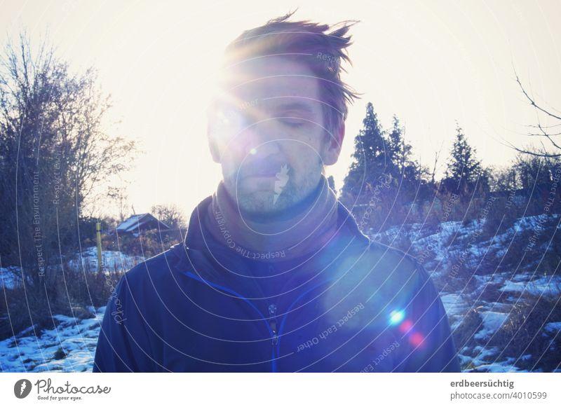 Mann beim Sonnetanken Strahlen Gesicht Haare kalt frostig wärmend geschlossene Augen Blendflecken blau entspannt genießen träumen Landschaft Winter Bäume