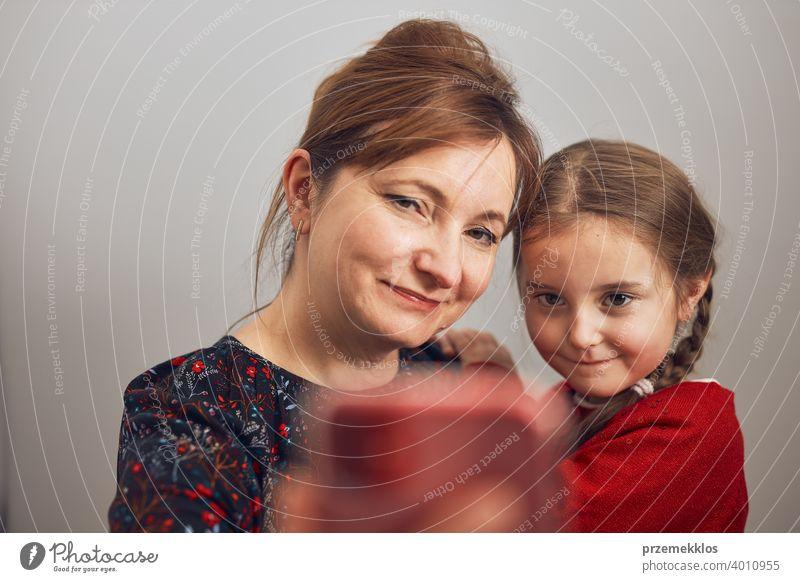 Mutter mit ihrer kleinen Tochter machen Videoanruf mit Handy. Frau und kleines Mädchen im Gespräch mit Verwandten. Fröhliche Familie mit Spaß nehmen selfie Foto mit Smartphone