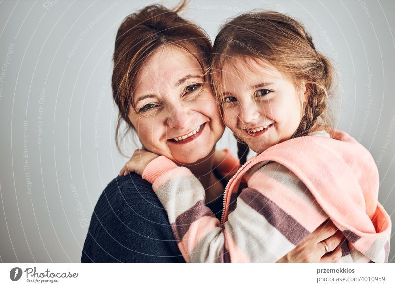Glückliche Mutter und Tochter umarmt, umarmt und lächelnd zusammen. Familienporträt. Glücklicher Moment. Frau und kleines Mädchen posieren zur Kamera Person
