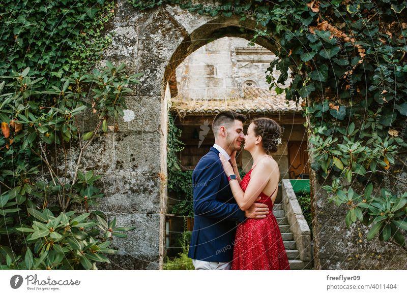 Elegantes junges Paar auf einem luxuriösen Gebäude mit Vegetation elegant Abschlussball Kuss 20s Kleid Anzug rot erstes Mal Veranstaltung Kaukasier Reichtum
