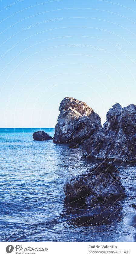 Meeresufer in der Nähe eines Berges mit Felsen und kleinen Wellen Bucht Strand Grundgestein blau Körper Klippe Küste Küsten- und ozeanische Landformen Formation