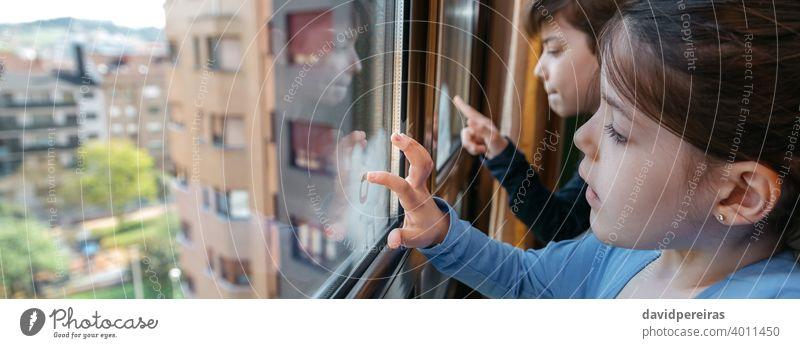 Zwei Kinder in Coronavirus-Sperre malen am Fenster Sperrung covid-19 Schreiben mit dem Finger panoramisch Textfreiraum Panorama Quarantäne Transparente Spielen