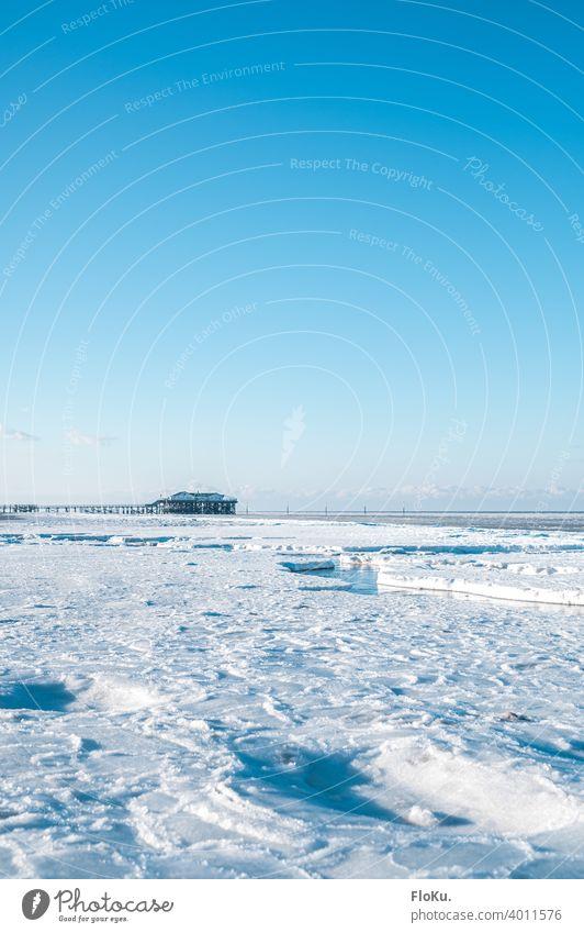 Winter mit viel Eis in Sankt Peter-Ording Strand Nordsee Küste Meer Einsamkeit Sonne Wellen Sand Wasser kalt Himmel blau Ebbe Ferne Horizont