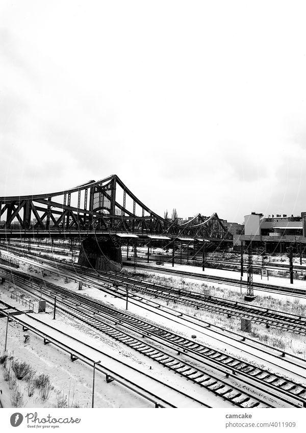 Brücke am Bahnhof mit Schienennetz im Schnee Spuren Bahnanlage urban Stadt Winter Zug Schwarzweißfoto Hochformat Grauwert Licht Digitalfotografie Kontrast