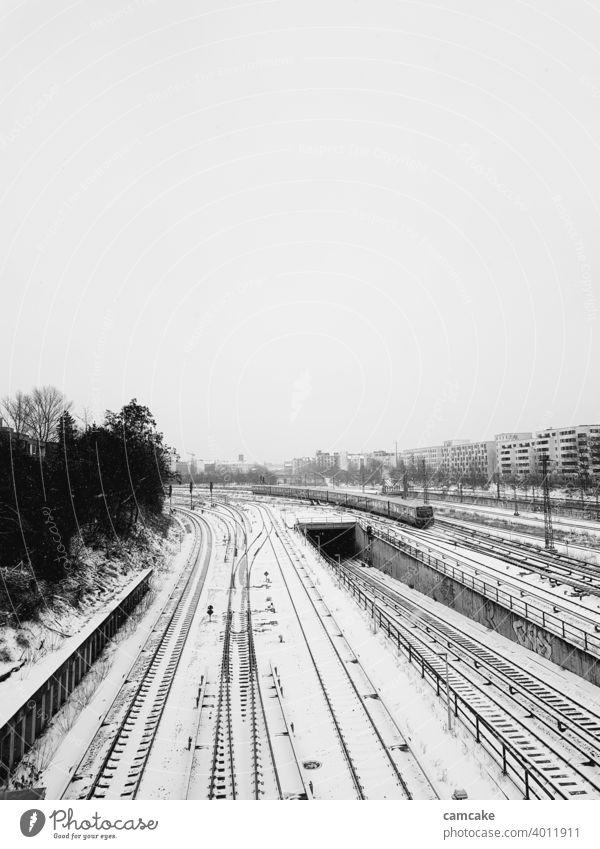 Zug auf Schienennetz am Bahnhof im Schnee Straßenbahn Kurve Netzwerk Stollen Schienenverkehr Linien kalt schneebedeckt weiß schwarz Eisenbahn Industrie