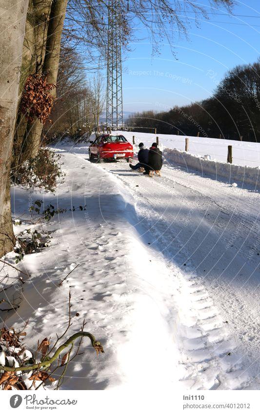 rotes Auto zieht Schlitten mit zwei Personen durch schneebedeckte Winterlandschaft Winterfreude Winterfreuden verschneite Straße verschneite Landschaft