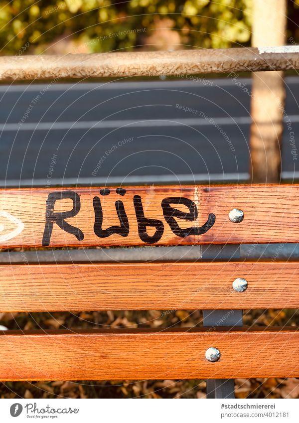 Wort Rübe auf Parkbank Bank Text Farbfoto Außenaufnahme Menschenleer Schmiererei Schriftzeichen Graffiti Straßenkunst Jugendkultur Tag Buchstaben