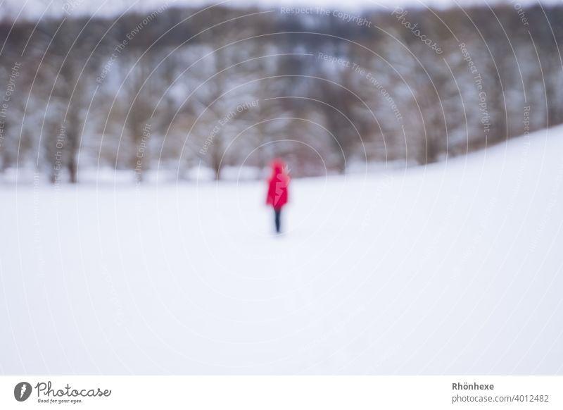 """Ein """"Geist""""  in roter Jacke beim Winterspaziergang unscharf fotografiert Unschärfe Mensch Farbfoto Außenaufnahme Tag Schnee weiß Winterlicht Landschaft Umwelt"""