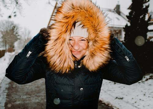 Frau spaziert bei Schneefall durch die Straßen spaziergang Spaziergang Winterspaziergang Kaminsims kunstpelz lachen lächeln Wärme schneefall Schafe Kälte weiss