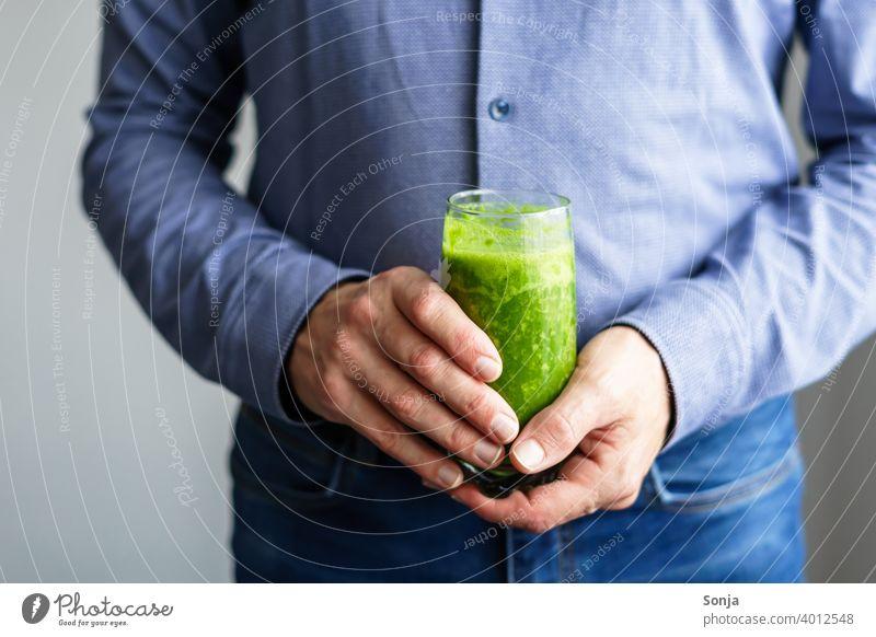 Mann hält ein Glas grünen Smoothie in seinen Händen smoothie 50 plus Hemd Jeanshose Teilansicht Hand halten Business Gesunde Ernährung Vitamin Diät