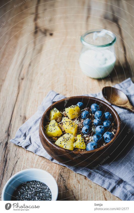 Gesundes Frühstück mit Müsli und Obst Haferflocken Heidelbeere Ananas Früstückstisch Gesunde Ernährung superfood Foodfotografie Tisch Holz rustikal Diät