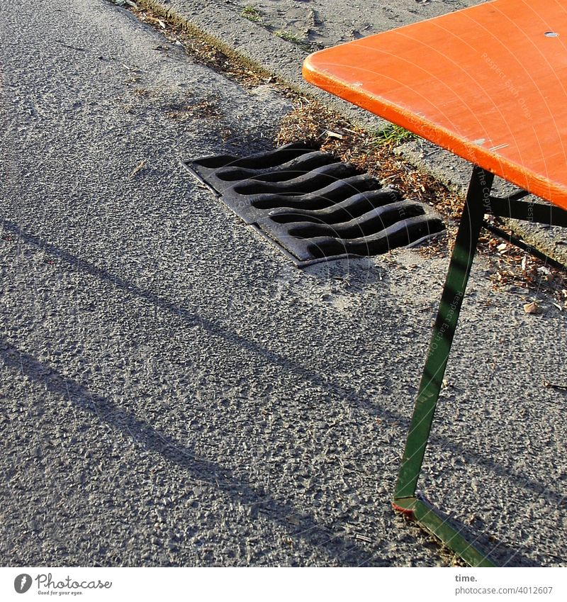 End of Flohmarkt tisch straße gully asphalt abfluss klapptisch schatten bordstein holz metall orange grau laub herbstlaub