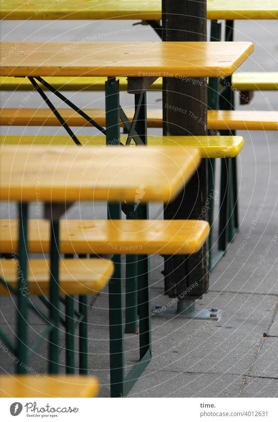 Bankgeschäfte, schlecht laufend | corona thoughts Sitzbank bierbank tisch biertisch gastronomie außengastronomie leer einsam gelb metall holz gehwegplatten