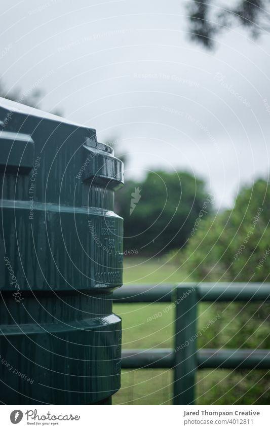 Ein Regenwassertank auf dem Land bekommt eine Dusche. Tank Wasser fluten Unwetter Wolken Australien Dorf Zaun im Freien Natur grün wolkig stürmisch kalt Wetter