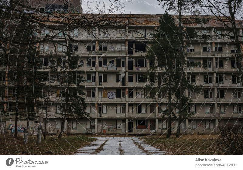 Verlassenes Appartmentgebäude mit Graffiti darauf und Kiefern drum herum verlassenes Gebäude Landschaft verlassene Straße verlassener Ort