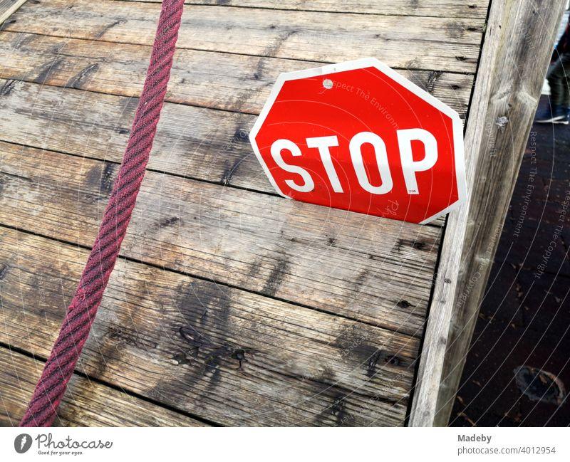 Stoppschild aus Blech in der Ritze einer Holzpritsche mit rotem Seil auf einem Kinderspielplatz an der Grundschule in Wettenberg Krofdorf-Gleiberg bei Gießen in Hessen