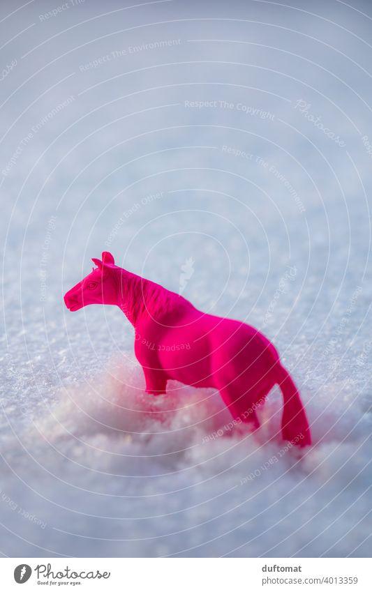 Pinkes Spielzeug Pferd im Schnee Neon pink Radiergummi Tier draußen bedeckt Schneelandschaft Schneedecke Winter alleine kalt weiß Natur Außenaufnahme neonfarbig