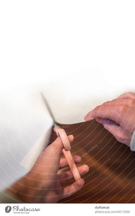Vogelperspektiv auf Hände, die mit Schere ein großes weißes Papier zerschneidet. Hand menschliche hand schneiden zerteilen trennen Finger Nahaufnahme Mann Haut