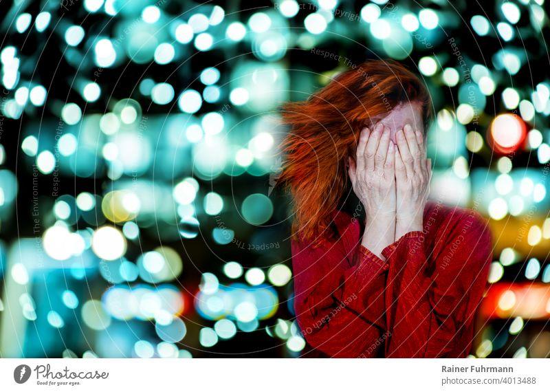 Eine rothaarige Frau hält sich die Hände vor das Gesicht. Im Hintergrund leuchtet das Bokeh heller Lichter. Probleme Kopfschmerzen abstrakt Unschärfe