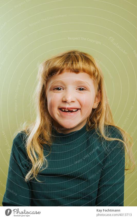 Porträt eines lachenden blonden Mädchens vor grünem Hintergrund Pony blondes Haar Freizeitkleidung Kind Kindheit farbiger Hintergrund niedlich Tochter Emotion
