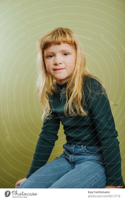Porträt von niedlichen blonde Mädchen gegen grünen Hintergrund Pony blondes Haar Freizeitkleidung Kind Kindheit farbiger Hintergrund Emotion grüner Hintergrund