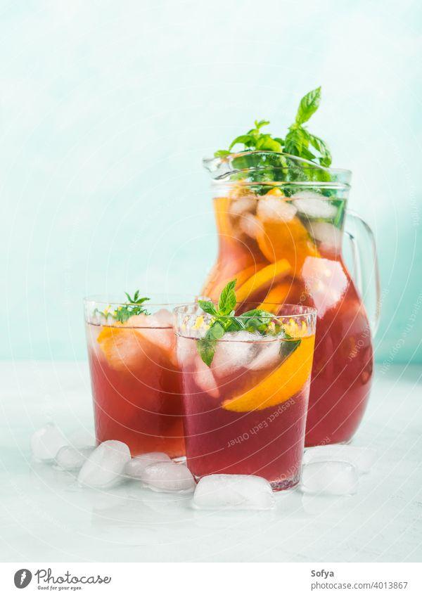 Frischer roter Coktail-Sangria in Krug und Gläsern Cocktail Mocktail trinken Wein Zitrusfrüchte orange Limonade Zitrone Frucht Sommer Dekor Blatt Glas Saft
